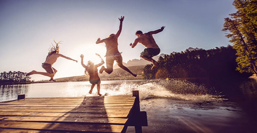 people jumping off dock into a lake