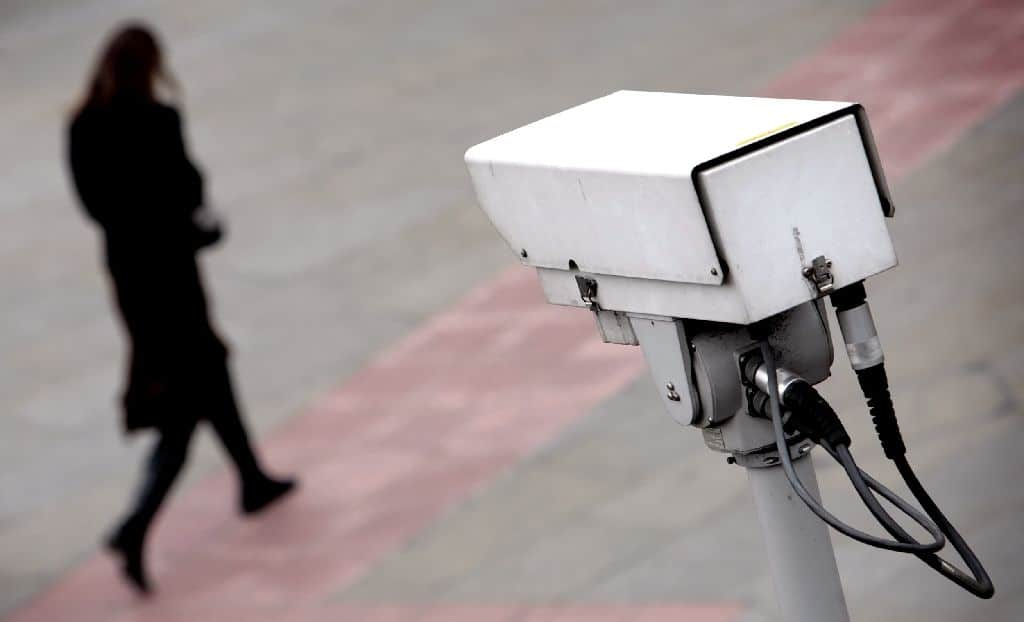 photo of a surveillance camera and someone walking by it