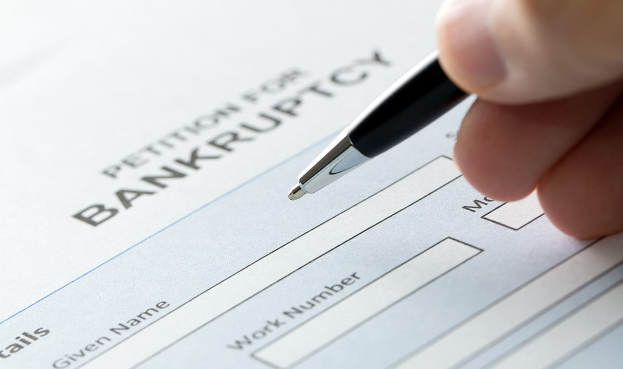 picture of a hand filling out bankruptcy form