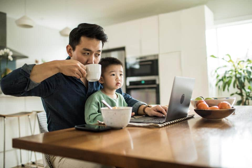 photo of a man working from home with his child